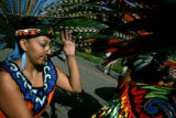 Karla Lopez, 26, of Denver, moves feathers from another headdress from her eyes before the...