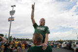 Derek Streeter, 23, (cq) is lifted up by Aaron Culbertson, 22, (cq) during a tailgate in the...