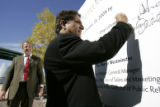 (L-R)  Dr. Deepak Chopra, (right) signs his name on a project mural Thursday afternoon, October...