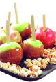 A plate of caramel apples and caramel popcorn for a Halloween party treat.  Making caramel apples...