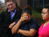 Lyn Kulenburg (cq), left, a victim of a robbery, consoles Miranda Macias (cq), center, outside the...
