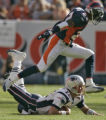 Denver Bronco's corner back, Domonique Foxworth, top, leaps over a downed New England Patroits'...