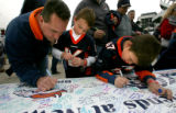 "Scott Ludvik, cq, 35, left, of Littleton signs a ""Get Well"" banner for Denver Broncos..."