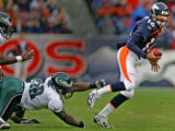 Denver Broncos quarterback Jake Plummer scrambbles out of the grasp of Philadelphia Eagles trent...