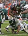Denver Broncos Mike Anderson leaps over Brian Dawkins for a two yard touchdown run in the first...