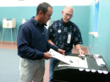 Albert Nicholson Garrett IV (cq) deposits his vote while Election Judge Conrad Gutierrez (cq),...