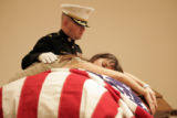 Inside the mortuary, Katherine Cathey draped herself over her husband's casket as Major Steve Beck...