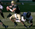 University of Colorado quarter back, Joel Klatt rolls out of the pocket and escapes being sacked...