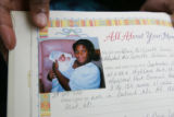 Lynette Thompson (Cq), holds her daughter's baby book that Lynette carefully made, showing the...