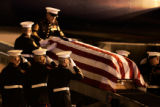 Marines from Buckley Air Force Base salute as the casket of a fallen Marine is lowered from the...