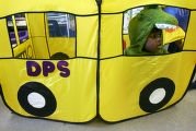 Dressed in a dinosaur costume, Malachi Groff (cq), 5, plays in a DPS bus in a Colorado Preschool...