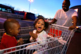 Dayshone Sylvester, 1, cq, left, and Kaelyn Elzy, 3, cq,  ride in a shopping cart pushed by Elzy's...