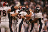 JPM1412 -- Denver Broncos kicker Jason Elam, #1, is swarmed by teammates including Mike Leach,...