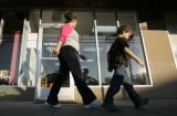 Pedestrians walk past  the storefront of the Los Alamos Alliance with Lockheed Martin and...