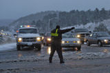 A Jefferson County Sheriff officer redirects traffic after the cars were forced off I-70 after...