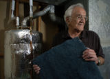 George Kelaidis (cq) stands next to his insulation covered water heater and holds a washable...