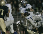 Poudre High School running back Tanner Ehrlich, #5 white, spins in the air on his way to scoring...