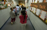 First graders walk down a hallway decorated for Thanksgiving at Castro Elementary School...