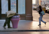 Local Denver panhandlers how goes by the name of Johnney looks for food in a trash can at 16th...