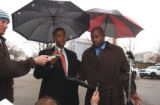 (L to R holding umbrellas) Aurora police Sgt. Rudy Herrera (cq) and officer Marcus Dudley (cq)...