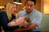 SPECIAL TO THE ROCKY MOUNTAIN NEWS  Vanessa Piedra, left, hands her new daughter, Eva, 7 weeks...