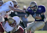 Holy Family running back Tim Stockhausen,right, spins past Faith Christian defenders Kevin...