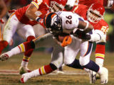 Denver Broncos Tatum Bell gets tackled by Kansas City Chiefs Sammy Knight while getting a first...