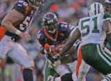 Denver Broncos running back Tatum Bell, middle, splits defenders for a 6 yard gain in the third ...