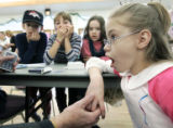 Kaymie Bullock, (cq) right, 11 reacts to a card trick by magician Lawrence Crowley (cq) at a...