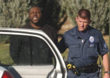 Patrick Scott is taken to an Aurora Police car after the Aurora SWAT team  was called to the...