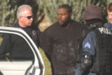 Patrick Scott (center) is taken away by police after the Aurora SWAT team  was called to the...