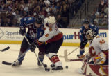 Andrew Brunette slips the puck past Calgary's Jordan Leopold but not past goalie Philippe Sauve in...