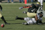 University of Colorado tail back Byron Ellis,left, looks to recover a fumble after hitting...