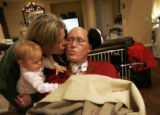 Kathy Slade (cq) gives her husband Scott Slade (cq) a kiss while holding one of their twin...