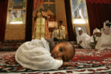 0433 A child lays in front of the church while member of the Debre Salam Medhanealem Ethiopian...