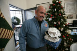 Joe Lucero brings in presents and food from a guest at  a holiday party at his home in Aurora,...