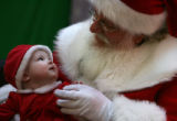 MJM440 Eva Byalskiy, 7 months, of Greenwood Village, Colo. gazes up at Santa Claus while making a...
