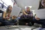School Review Team member Pat Termin (cq, center), a retired teacher and principal, listens in on...