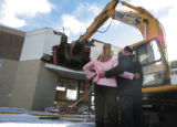 In front of a partially demolished store front City Council Member Molly Markert embraces Mayor Ed...