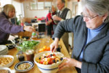 Susan Booker mixes the fruit salad on the center island of the community kitchen in the Silver...