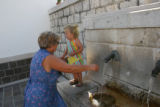 Photo by John Sopinski     Maria Lombardi test the water from the fountain as she holds onto...