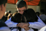 DM0395   Angel Martinez, center facing camera, gets a hug after loading the casket of his sister,...