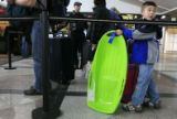 DM0683   Zachary Gordon tows his sled along with his suit case as he waits in line to check-in for...