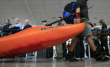 DM0785   Patrick Rogers, 22, of Steamboat Springs drags his kayak through the line to check-in for...