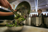 Laurie Travers (cq) watches as Amanda Massey (cq) salad maker at Mad Greens mixes it up across...