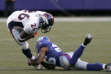 Tatum Bell is tackled by Brent Alexander in the 1st quarter of the Denver Broncos against the New...