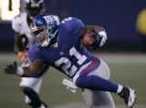 Tiki Barber tries to elude a tackle in the 3rd quarter of the Denver Broncos against the New York...