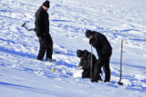 DM0091   Denver Police investigators  dig slugs out of the snow covered hillside in front of a...