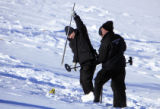 DM0127   Denver Police investigators  dig slugs out of the snow covered hillside in front of a...