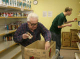 Volunteer Eldon Hemmingsen (cq), left, puts some food in abox for a client, while fellow...